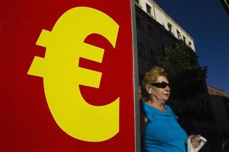 A woman walks past a banner showing an euro sign as part on an advertisement for pizza sales outside a pizza store in Madrid August 1, 2012. REUTERS/Susana Vera/Files