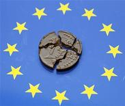 Разломленная шоколадная монета евро лежит на флаге ЕС в Любляне, 11 сентября 2012 года. Обстановка на денежных рынках еврозоны ухудшилась во втором квартале 2012 года, показало исследование Европейского центробанка, опубликованное в пятницу. REUTERS/Srdjan Zivulovic
