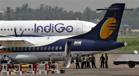 Airport staff stand next to parked passenger jets of IndiGo and Jet Airways (front) at an airport in Kolkata, in this file picture taken May 6, 2012. REUTERS/Rupak De Chowdhuri/Files