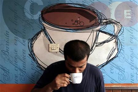 A man drinks coffee at a coffee shop in Mumbai May 9, 2006. REUTERS/Adeel Halim/Files