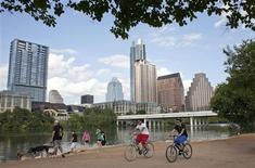 Cyclists pass beneath the downtown skyline on the hike and bike trail on Lady Bird Lake in Austin, Texas September 18, 2012. REUTERS/Julia Robinson