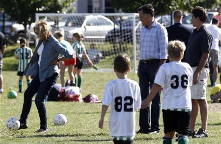 U.S. Republican presidential nominee and former Massachusetts Governor Mitt Romney (rear C) and his son Tagg (rear R) watch Ann Romney kick a soccer ball as they watch a children's soccer game in Belmont, Massachusetts, September 15, 2012. REUTERS/Jim Young