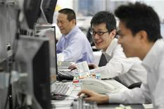 Foreign exchange dealers smile as they conduct trading at a dealing room in Tokyo October 31, 2011. REUTERS/Yuriko Nakao