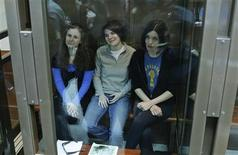 "Members of the female punk band ""Pussy Riot"" (L-R) Maria Alyokhina, Yekaterina Samutsevich and Nadezhda Tolokonnikova sit in a glass-walled cage before a court hearing in Moscow, October 1, 2012. The Moscow City Court on Monday hears an appeal by three jailed members of the band, who were sentenced to two years in prison for staging an anti-Kremlin protest at the Cathedral of Christ the Saviour, according to local media. REUTERS/Maxim Shemetov"