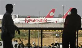 People are silhouetted as Kingfisher Airlines' aircrafts are seen parked at an airport in New Delhi October 1, 2012. Ailing Indian carrier Kingfisher Airlines will not be allowed to fly if safety rules are not followed, Civil Aviation Minister Ajit Singh said, after labour unrest forced the carrier to cancel its flights on Monday. REUTERS/Mansi Thapliyal