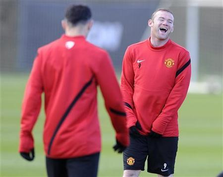 Manchester United's Wayne Rooney (R) reacts during a practice session at the clubs Carrinington training complex in Manchester, northern England March 7, 2012. REUTERS/Nigel Roddis/Files