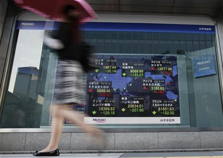 A woman walks past an electronic board displaying market indices outside a brokerage in Tokyo September 20, 2012. REUTERS/Yuriko Nakao
