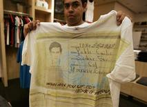 A salesperson shows a T-shirt with a picture of late Colombian cocaine kingpin Pablo Escobar at a store in Zapopan on the outskirts of Guadalajara September 28, 2012. Nearly two decades after Escobar died in a hail of bullets, his eldest son is conquering new markets in Mexico - with a fashion line in his father's image. Sebastian Marroquin's designer T-shirts, plastered with photos of Escobar, are hot sellers in Mexican states that are on the front lines of the country's deadly drug war. Picture taken September 28, 2012. REUTERS/Alejandro Acosta