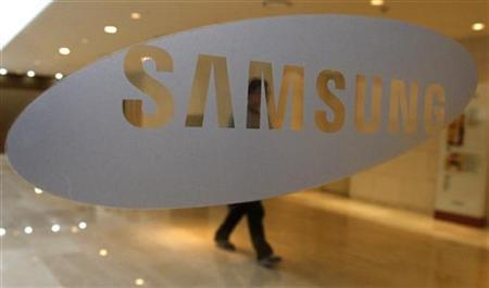 A man walks behind a logo of Samsung Electronics at the company's headquarters in Seoul April 30, 2010. REUTERS/Jo Yong-Hak