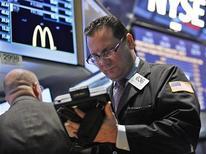 Трейдер работает в торговом зале Нью-Йоркской фондовой биржи, 1 октября 2012 года. Американские фондовые индексы завершили торги вторника разнонаправлено, поскольку инвесторы не знают, когда Испания планирует обратиться за международной финансовой помощью. REUTERS/Brendan McDermid