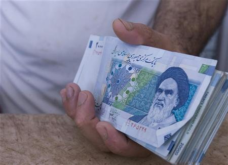 A butcher holds money in a butcher's shop in Islamshahr, 50km (31 miles) southwest of Tehran March 5, 2008. REUTERS/Raheb Homavandi