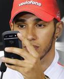Piloto de Fórmula 1 Lewis Hamilton verifica telefone celular durante coletiva de imprensa no Japão. Hamilton fez bem em sair da McLaren se deseja ganhar mais títulos na Fórmula 1, disse seu ex-colega de equipe Fernando Alonso na quinta-feira. 04/10/2012 REUTERS/Kim Kyung-Hoon