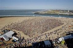"Some of around 10,000 people take part in the filming of ""The big ask again"" video clip on a beach at Oostende August 29, 2009. REUTERS/Sebastien Pirlet"