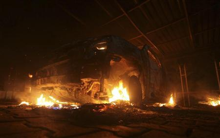 A burning car is seen at the U.S. Consulate in Benghazi during a protest by an armed group said to have been protesting a film being produced in the United States September 11, 2012. REUTERS/Esam Al-Fetori