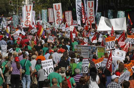 Demonstrators holding banners protest against further tax hikes and austerity cuts in Madrid October 7, 2012. REUTERS/Andrea Comas