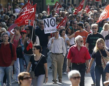 A demonstrator holds a banner as he joins others during a protest against further tax hikes and austerity cuts in Madrid October 7, 2012. REUTERS/Andrea Comas