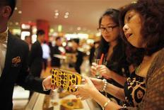 Женщины смотрят кошелек в магазине в Шанхае, 7 сентября 2012 года. Рост сектора услуг Китая восстановился в сентябре после замедления до годового минимума в августе, свидетельствует частное исследование, появившееся после выхода более мрачных официальных данных. REUTERS/ Carlos Barria