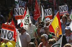 Демонстранты держат плакаты во время акции протеста против повышения налогов и сокращения бюджетных расходов в Мадриде, 7 октября 2012 года. Министры финансов еврозоны в понедельник запустят постоянный фонд помощи объемом 500 миллиардов евро ($653 миллиарда), призванный стать серьезным инструментом защиты от долгового кризиса. REUTERS/Andrea Comas