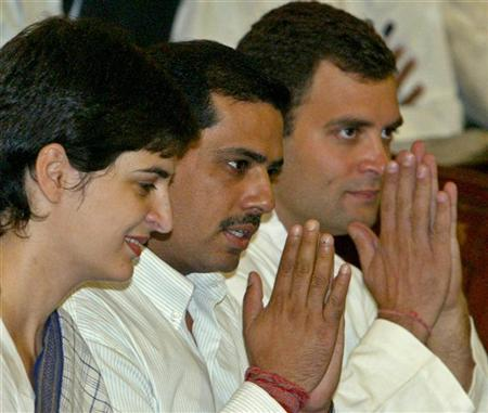 Rahul Gandhi (R) flanked by his brother-in-law Robert Vadra (C) and sister Priyanka Vadra greets his party lawmakers inside the central hall of Indian parliament in New Delhi May 18, 2004. REUTERS/Kamal Kishore AH/THI