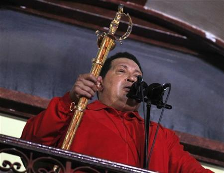 Venezuelan President Hugo Chavez holds the sword used by former Venezuelan military leader Simon Bolivar while celebrating from a balcony at Miraflores Palace in Caracas October 7, 2012. REUTERS/Tomas Bravo