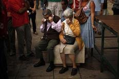 Испанские пенсионеры вытирают слезы во время акции протеста против повышения налогов и сокращения госрасходов в Малаге, 7 октября 2012 года. Международный валютный фонд сократил прогнозы экономического роста второй раз с апреля и предупредил американских и европейских регуляторов, что неспособность решить экономические проблемы продлит спад. REUTERS/Jon Nazca