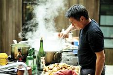 """Charles Phan, chef and author of """"Vietnamese Home Cooking"""", prepares a meal outdoors in Northern California in this undated handout photograph. REUTERS/Eric Wolfinger/Handout"""