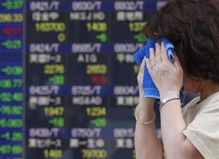 A woman wipes her face with a towel as she passes an electronic board displaying share prices in Tokyo August 31, 2012. REUTERS/Yuriko Nakao