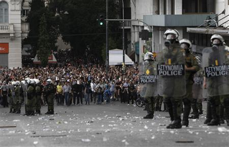 Riot police stand guard in front of demonstrators during a protest against the visit of Germany's Chancellor Angela Merkel, in Athens October 9, 2012. REUTERS/John Kolesidis