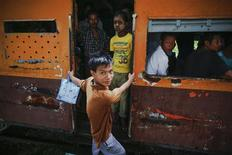 A young man hangs from a moving train in Yangon's suburbs September 17, 2012. REUTERS/Damir Sagolj