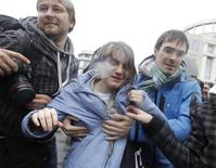 """Yekaterina Samutsevich (C), a member of the female punk band """"Pussy Riot"""", walks after she was freed from the courtroom in Moscow October 10, 2012. Samutsevich was freed on appeal on Wednesday but a Moscow court upheld prison sentences for two others imposed over a raucous cathedral protest against Vladimir Putin, who said they had got the jail terms they deserved. REUTERS/Maxim Shemetov"""
