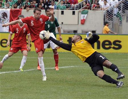 Wales goalkeeper Jason Brown makes a save as Wales' Chris Gunther helps out during the first half of their international friendly soccer match against Mexico in East Rutherford, New Jersey, May 27, 2012. REUTERS/Bill Kostroun/Files