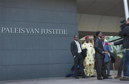 Representatives of both farmers and fishermen from Nigeria are interviewed by a Dutch television crew in front of a local court in The Hague October 11, 2012. REUTERS/Michael Kooren