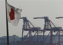 Японский флаг в промышленном порту в Токио, 20 сентября 2012 года. Правительство Японии снова понизило оценку экономики, так как опасения, касающиеся долгового кризиса в Европе и спада в Китае, усилились, повышая риск для прогноза роста. REUTERS/Kim Kyung-Hoon