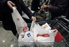Покупатель кладет в тележку пакеты с продуктами в римском супермаркете, 29 декабря 2010 года. Крупный российский продуктовый ритейлер Окей увеличил продажи на 26,1 процента в годовом выражении до 27,54 миллиарда рублей за третий квартал 2012 года, сообщила компания в пятницу. REUTERS/Alessia Pierdomenico
