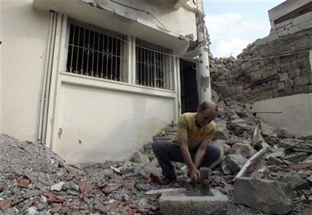 A man works in front of a damaged house near Homs October 9, 2012. Picture taken October 9, 2012 REUTERS/Yazan Homsy