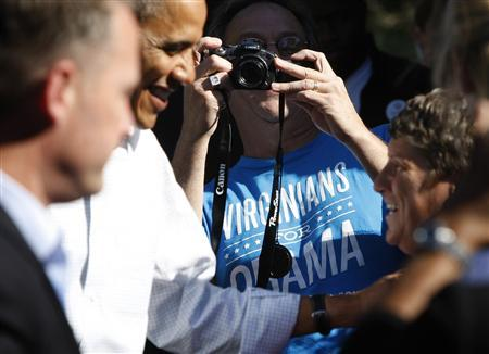 A supporter wearing a ''Virginians for Obama'' shirt takes a picture of U.S. President Barack Obama (L) as he greets supporters at his campaign office in Williamsburg, Virginia, October 14, 2012. REUTERS/Jonathan Ernst