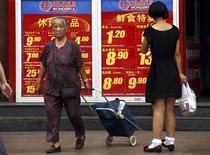 Пешеходы проходят мимо рекламного объявления торгового центра в Пекине, 9 августа 2011 года. Данные о сентябрьской инфляции в Китае подтвердили, что поддерживающие рост меры Пекина набирают обороты, и предоставили регуляторам больше возможностей для дальнейшего смягчения политики. REUTERS/David Gray