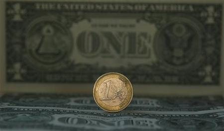 A one Euro coin is placed over one dollar notes in this illustrative photograph taken in Madrid November 17, 2011. REUTERS/Sergio Perez
