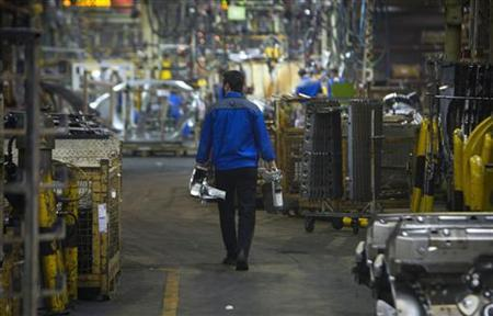 An Iranian worker carries car parts as he walks near a production line of carmaker Iran Khodro, west of Tehran June 20, 2011. REUTERS/Morteza Nikoubazl