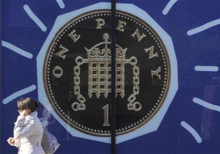 A pedestrian walks past an illustration of a one penny coin displayed in the window of a building in London March 23, 2011. REUTERS/Toby Melville
