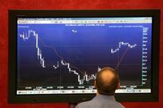 Трейдер смотрит на рыночный график на бирже ММВБ в Москве, 23 мая 2006 года. Российский фондовый рынок во вторник вновь слабо колеблется, не решаясь выбрать направление движения, за исключением акций Холдинга МРСК, продолжающих стремительное падение под давлением информации о цене допэмиссии. REUTERS/Alexander Natruskin