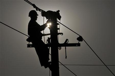 A worker repairs an utility pole on the outskirts of Yingtan, Jiangxi province December 28, 2010. REUTERS/Stringer/Files