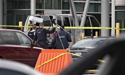 Police officers gather around the van where a man shot a Canadian Border Agent at the Peace Arch Canadian-U.S. border crossing in Surrey, British Columbia October 16, 2012. REUTERS/Andy Clark