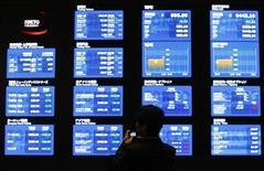 Мужчина фотографирует экраны с рыночной информацией на Токийской фондовой бирже, 11 апреля 2012 года. Азиатские фондовые рынки выросли в среду благодаря надежде инвесторов на хороший сезон квартальной отчетности компаний. REUTERS/Toru Hanai