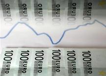 Банкноты евро и валютный график отражаются в стекле. Фотография сделана в Зенице 22 января 2011 года. Евро поднялся до месячного максимума к доллару после того, как рейтинговое агентство Moody's подтвердило инвестиционный рейтинг Испании. REUTERS/Dado Ruvic