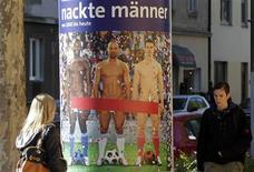 "Women pass by a poster with naked soccer players covered with a red paper stripe, advertising an art exhibition in Vienna October 17, 2012. Vienna's Leopold Museum has decided to cover the ""intimate parts"" of three naked male soccer players on large posters put up in the Austrian capital after they caused an outcry. The ""Naked Men"" exhibition, which opens on Friday and runs until January 28, 2013, is designed to show how the depiction of male nudity has evolved in art history. Around 300 art works - including the controversial photograph by French artists Pierre & Gilles called ""Vive La France"" of three men of different races wearing nothing but blue, white and red socks and soccer boots - will be on display. REUTERS/Herwig Prammer"