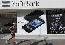 A jogger runs past a Softbank shop in Tokyo October 16, 2012. REUTERS/Kim Kyung-Hoon
