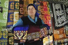 Женщина торгует традиционными текстильными изделиями на рынке в Ашхабаде 8 февраля 2012 года. Туркмения, удостоившаяся похвалы США за отказ от использования детского труда в уборке хлопка, собирается вложить свыше $1 миллиарда в ориентированную на экспорт текстильную промышленность, сообщил член правительства. REUTERS/Aman Mehinli
