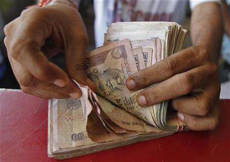A grocery shop owner counts rupees notes in Ahmedabad May 23, 2012. REUTERS/Amit Dave/Files