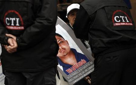 A woman holds a banner with a picture of a family member kidnapped by FARC rebels, during the National Convention of victims, while talking with Cuerpo Tecnico de Investigaciones (CTI) agents October 14, 2012. REUTERS/Fredy Buile